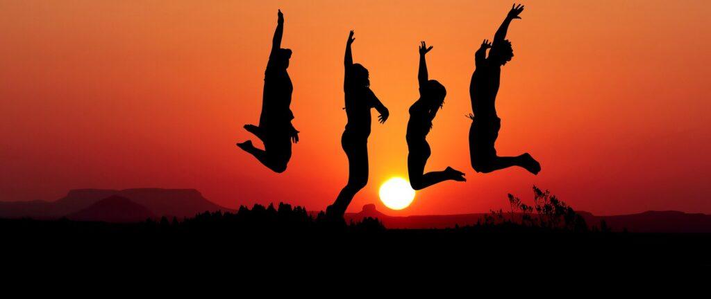 Bild av unga som hoppar mot en soluppgång